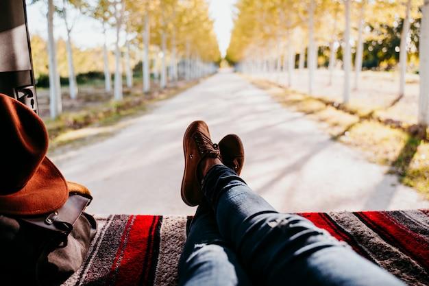 Gambe sveglie del cane e della donna di jack russell che si rilassano in un furgone. concetto di viaggio. messa a fuoco selettiva sugli alberi