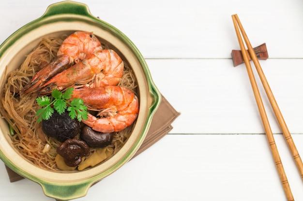 Gamberetti al forno con pasta di vetro o vermicelli in una pentola di terracotta, bacchette, una piccola tazza di salsa di immersione.
