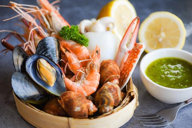 Gamberetti freschi gamberi calamari cozze maculato babilonia crostacei granchio e salsa ai frutti di mare limone su lastra di pietra nera sullo sfondo