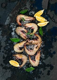 Gamberetti freschi non cotti con limone, erbe e spezie su ghiaccio scheggiato su pietra scura dell'ardesia