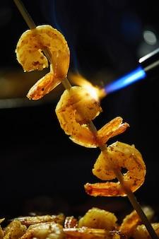 Gamberetti infilati su uno spiedino e fritti con un bruciatore su sfondo nero