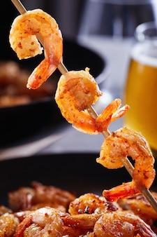 Gamberetti infilati su uno spiedino. gamberetti fritti in padella con aglio e limone su un piatto nero e un bicchiere di birra