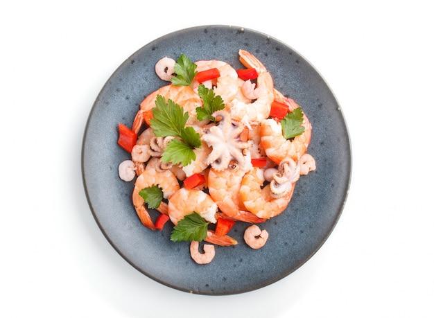 Gamberetti o gamberi bolliti e piccoli polpi con erbe su un piatto di ceramica blu isolato su sfondo bianco