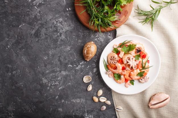 Gamberetti o gamberi bolliti e piccoli polpi sul piatto di ceramica bianco su uno sfondo di cemento nero e tessuto di lino