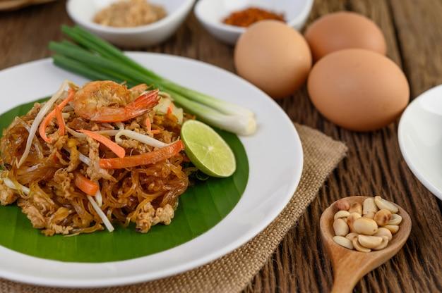 Gamberetto di padthai in un piatto bianco con calce e le uova sulla tavola di legno.