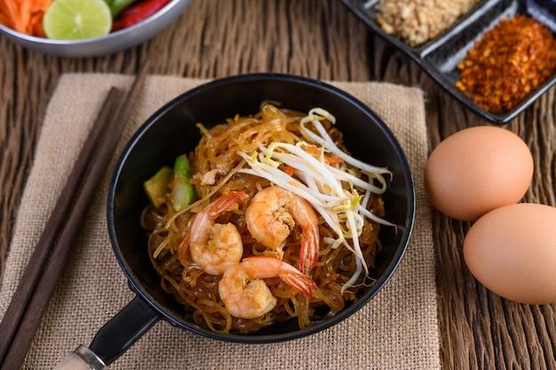 Gamberetto di padthai in una ciotola nera con le uova e condimento sulla tavola di legno.