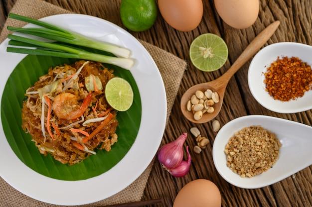 Gamberetto di padthai in una ciotola nera con le uova, la cipolla di inverno e il condimento sulla tavola di legno.