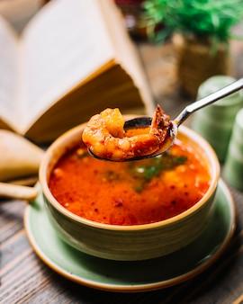 Gamberetto nella vista laterale del pane al pomodoro dei gamberetti della minestra di frutti di mare del cucchiaio