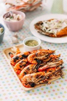 Gamberi alla griglia tailandesi (gamberi) con guscio e senza guscio serviti con salsa piccante in stile tailandese.