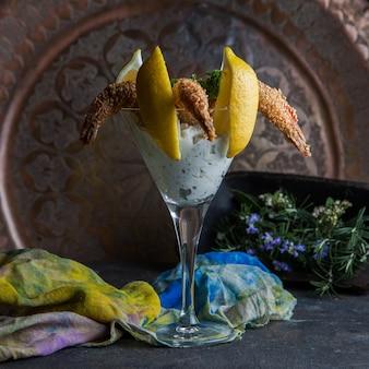 Gamberi con semi di sesamo con foglie di limone e rosmarino e straccio in un bicchiere da cocktail