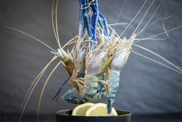 Gamberi crudi sulla ciotola con spezie limone sullo sfondo piatto scuro - gamberetti freschi per cibi cotti al ristorante o al mercato di pesce