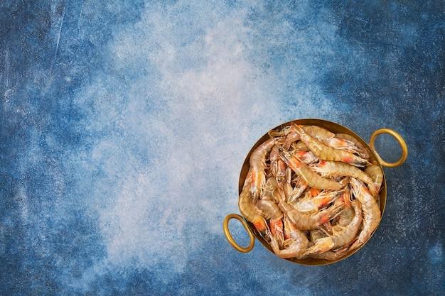 Gamberi freschi crudi su un piatto d'epoca su sfondo blu. copia spazio