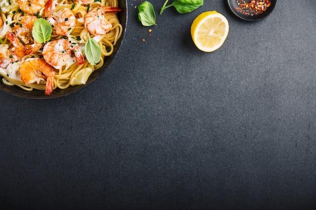 Gamberi freschi fritti con spezie sulla padella nera