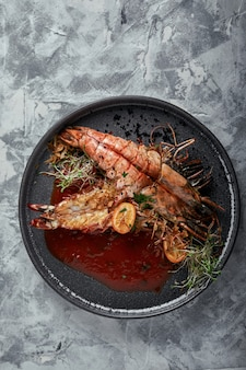 Gamberoni alla griglia, con salsa di pomodoro su una tonalità grigia e bassa. serie di calcestruzzo. cibo, stile alimentare, copyspace, riviste di pubblicità alimentare e social network.
