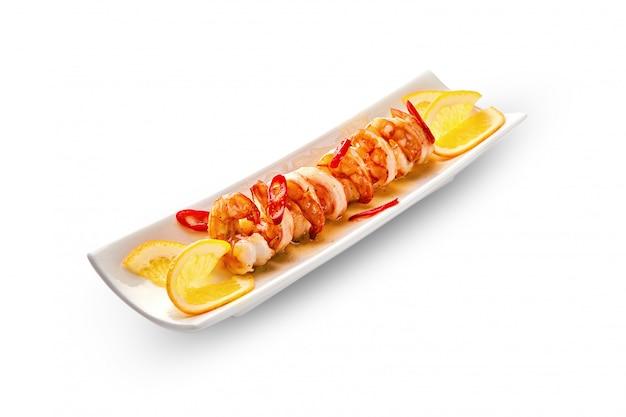 Gamberoni fritti in un piatto con salsa e le arance, con peperoncino, primo piano. zolla bianca su un isolato
