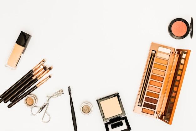 Gamma di colori di trucco dei cosmetici con il bigodino dei cigli e delle spazzole isolato su fondo bianco