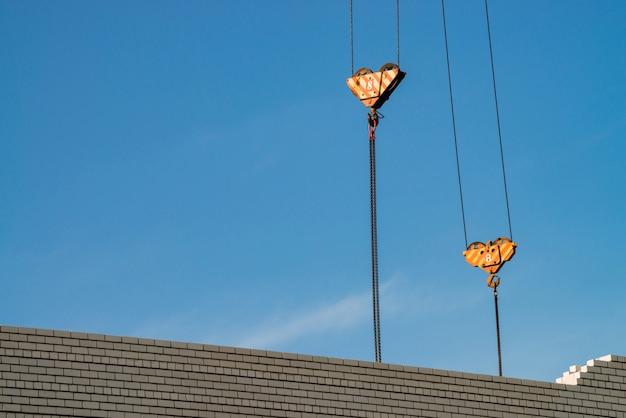 Gancio della gru a torre sopra costruzione non finita nel cantiere. immagine di sfondo del muro di mattoni bianco sotto cielo blu. immagine di sfondo di processo di costruzione.