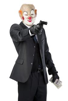 Gangster mascherato da clown con una pistola durante una rapina