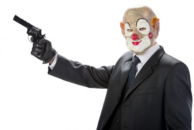 Gangster mascherato da clown con una pistola durante una rapina.