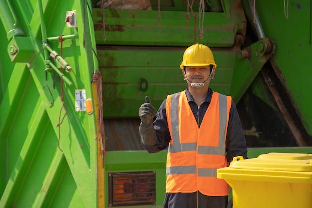 Garbage collector, felice lavoratore maschio con pattumiera in strada durante il giorno.