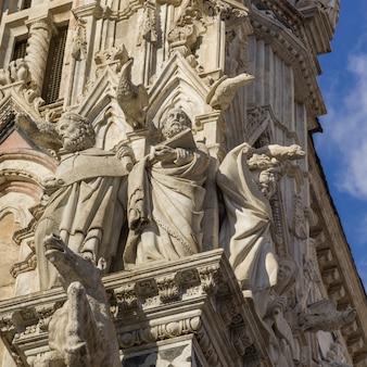 Gargoyles e san sulla facciata della cattedrale di siena, siena, toscana, italia