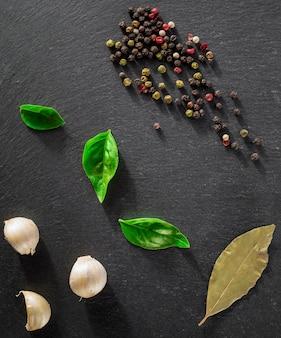 Garlick finocchio pepe di basilico su una pietra nera