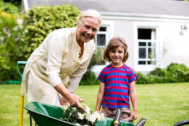 Garndmother e ragazzo con vasi di fiori in carriola