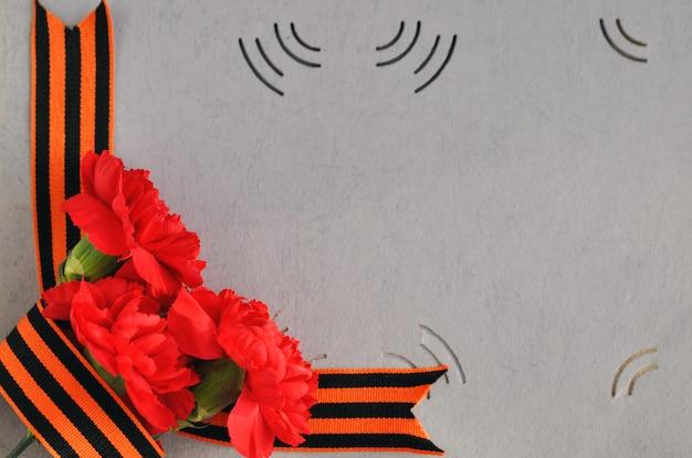 Garofani rossi e nastro di san giorgio sullo sfondo di un vecchio album di foto. giorno della memoria e della gloria militare.