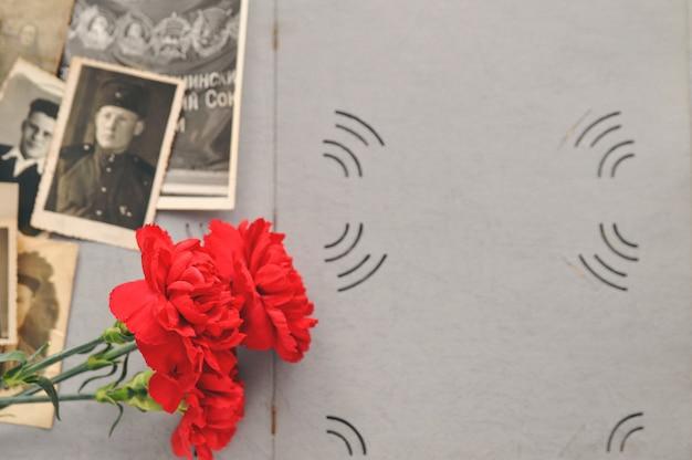 Garofani rossi sullo sfondo di un vecchio album di foto con foto militari. giorno della memoria e della gloria militare.