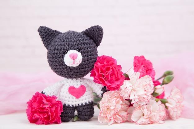 Gatto a maglia con un cuore. decorazioni di san valentino. giocattolo a maglia, amigurumi. biglietto di auguri di san valentino.