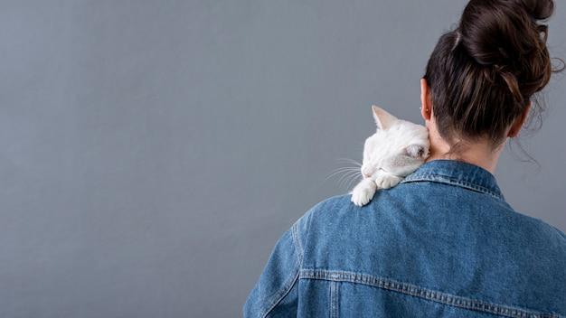 Gatto bianco che si siede sulla spalla femminile