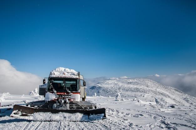 Gatto delle nevi rosso del ratrak in montagne di inverno