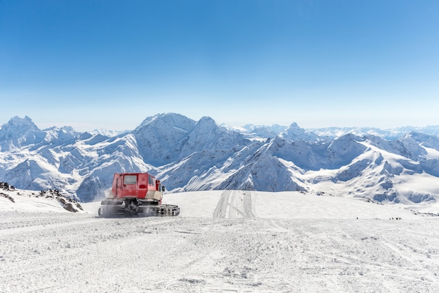 Gatto delle nevi su un pendio in alto nelle montagne