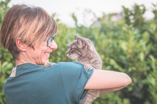 Gatto domestico allegro tenuto e coccolato dalla donna sorridente con gli occhiali