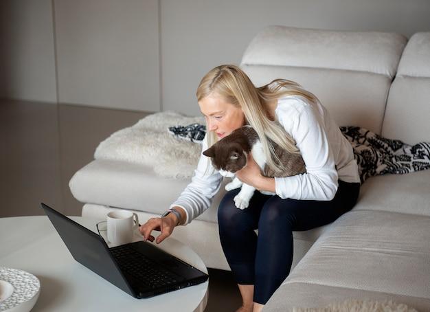 Gatto maturo della tenuta della donna e lavorare al computer portatile a casa sullo strato