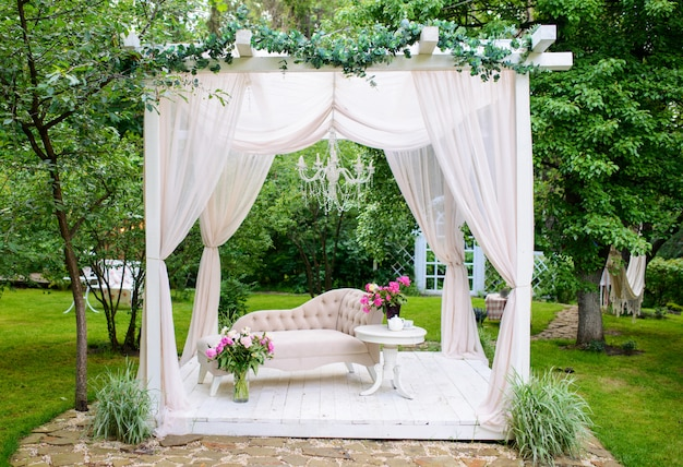 Gazebo estivo delicato ed elegante in rigogliosi giardini. squisito divano classico decorato con fiori in un gazebo con tende bianche nel fresco giardino