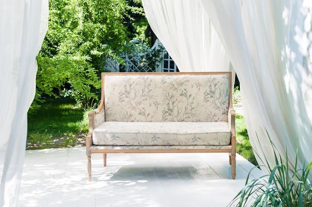 Gazebo moderno di lusso con mobili morbidi e tende all'interno del giardino. padiglione cerimonia di nozze estive.