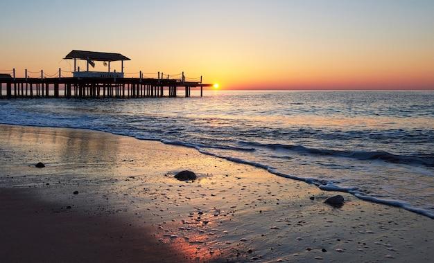 Gazebo sul molo in legno in mare con il sole al tramonto.
