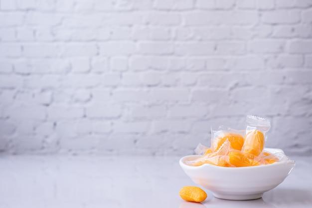 Gelatina di mango sul piatto bianco e sfondo di texture muro di mattoni bianchi.