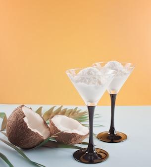 Gelato al cocco sullo sfondo blu e arancio con foglia di palma e cocco