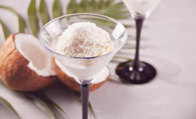 Gelato al cocco sullo sfondo grigio con foglia di palma e cocco