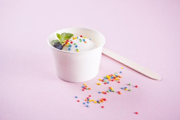 Gelato alla vaniglia con foglia di menta e caramelle colorate su sfondo rosa
