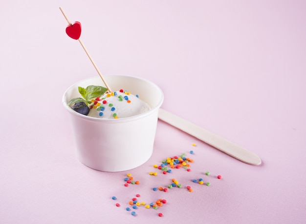 Gelato alla vaniglia con foglia di menta, fragole e mirtilli sul rosa
