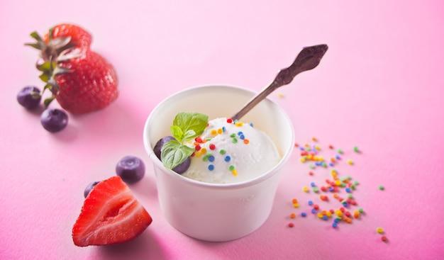 Gelato alla vaniglia con foglia di menta, fragole e mirtilli sullo sfondo rosa