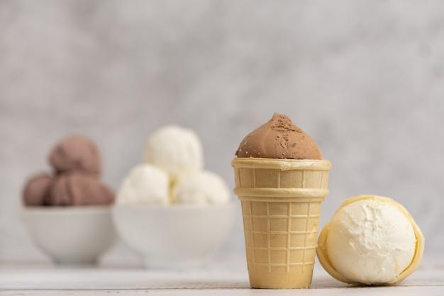 Gelato alla vaniglia e al cioccolato in una ciotola e coppe di cialda su sfondo chiaro. vista laterale