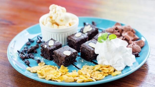 Gelato alla vaniglia e brownies su un piatto blu.