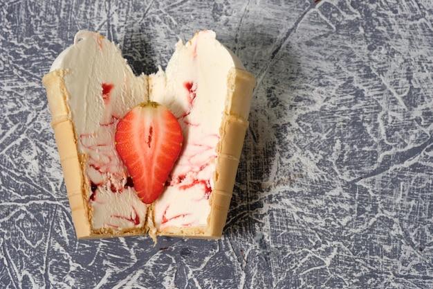 Gelato alla vaniglia in una tazza di cialda con frutta ripieno su uno sfondo grigio con fragole in un taglio