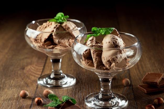 Gelato artigianale al cioccolato con foglie di menta, cosparso di cioccolato in una ciotola di vetro su un tavolo di legno