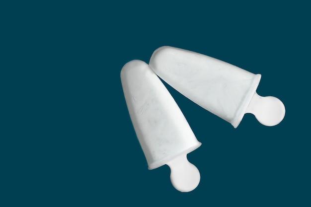 Gelato bianco fatto in casa su un classico tavolo blu, colore dell'anno. ghiacciolo allo yogurt naturale senza zucchero in una calda giornata estiva. primo piano, copia spazio