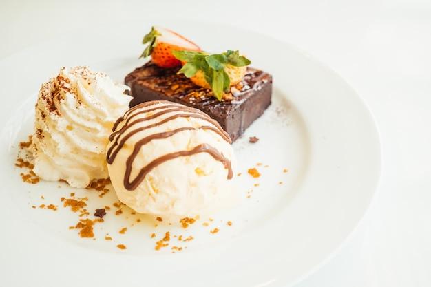 Gelato di vaniglia con torta di cioccolato brownie con fragola su